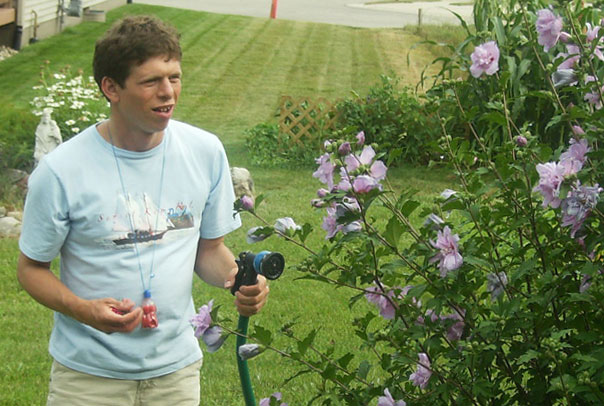 young man watering a bush of purple flowers with a hose